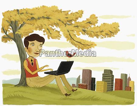 businessman using laptop under tree