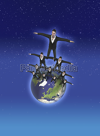 businessmen balancing on earth