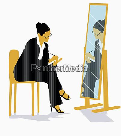 businesswoman looking in mirror