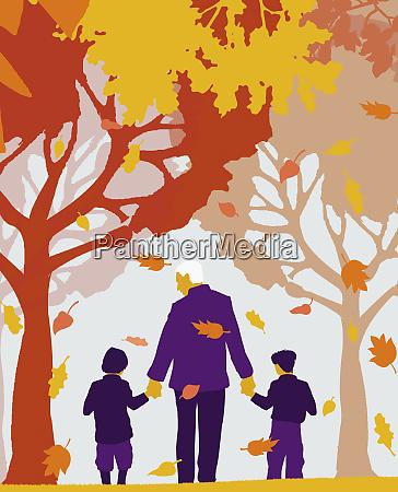 grandfather and grandchildren walking under autumn