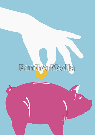 person putting coin into piggy bank