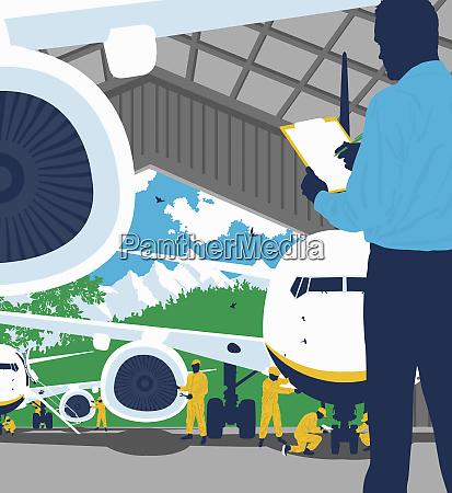 ingenieur mit zwischenablage ueberwacht flugzeugmechaniker