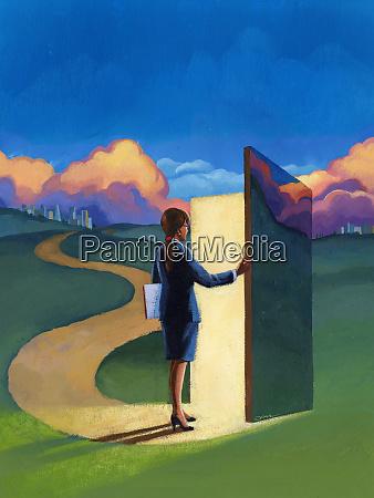businesswoman in field opening door in