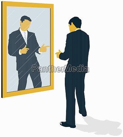 confident businessman looking at reflection and