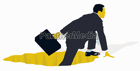 businessman with briefcase climbing out of