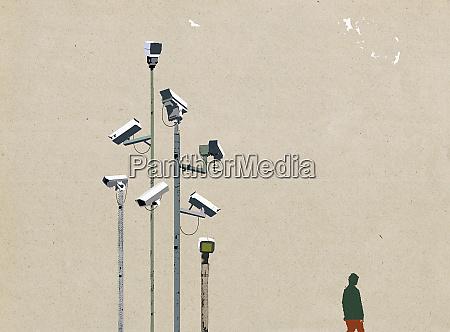 man waking beneath surveillance cameras