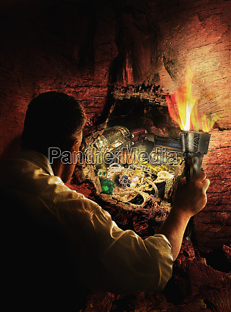 man with torch uncovering buried treasure