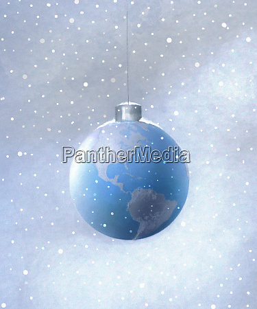 snow falling around hanging globe christmas