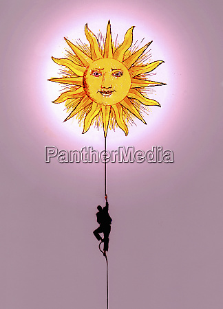 businessman climbing rope toward sun