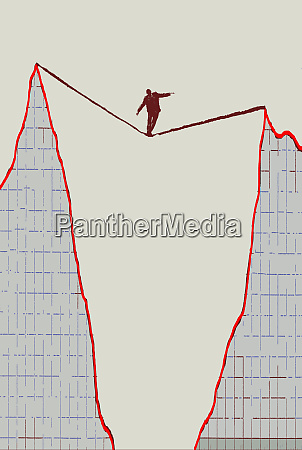 businessman walking tightrope between peaks on