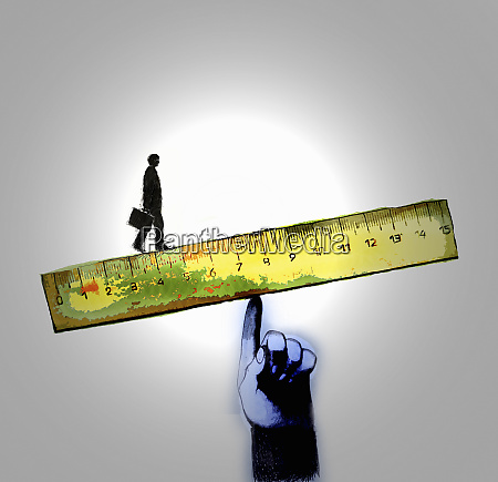 businessman walking on edge of ruler
