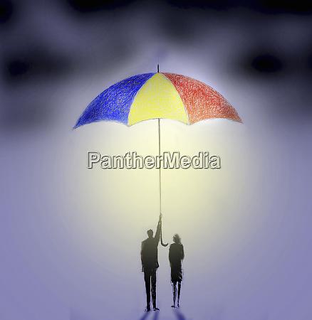businessman and businesswoman underneath large umbrella