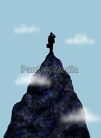 businessman using cell phone on mountain