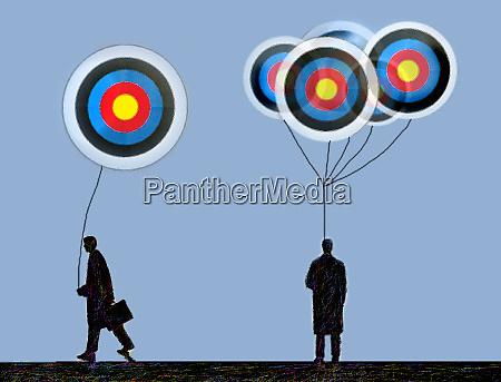 businessman receiving target balloon from bunch