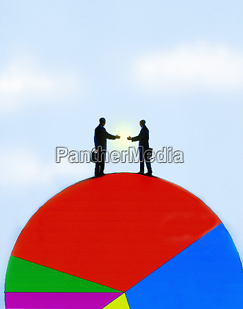 businessmen shaking hands on pie chart