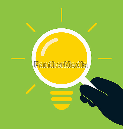 hand holding magnifying glass light bulb