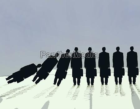 row of businessmen falling in domino