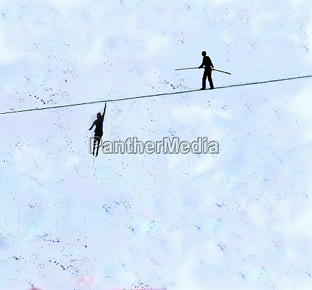 businesswoman hanging from tightrope while businessman