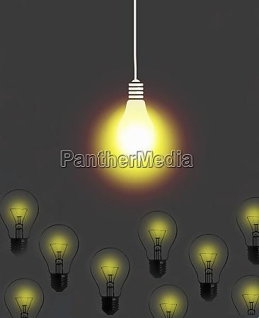 bright light bulb shining above dim