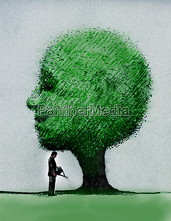 businessman watering smiling tree