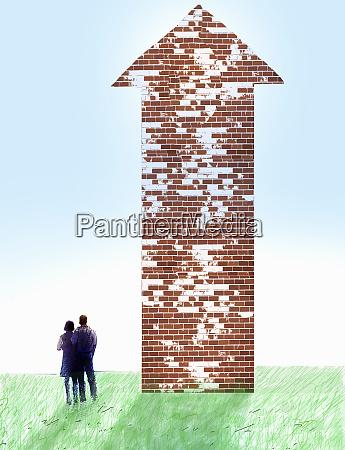 couple looking at brick wall arrow