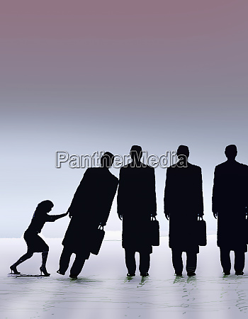 businesswoman pushing row of businessmen in