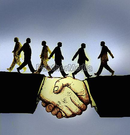 businessmen walking across handshake