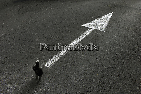 man standing looking at arrow painted