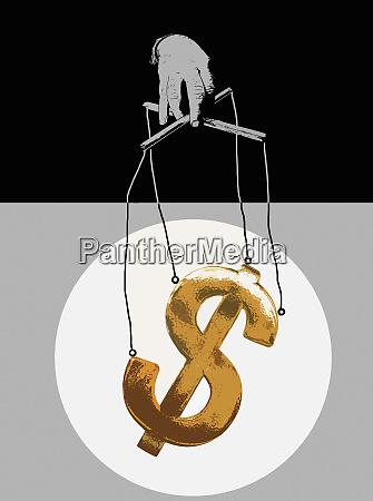 hand manipulating dollar symbol puppet on