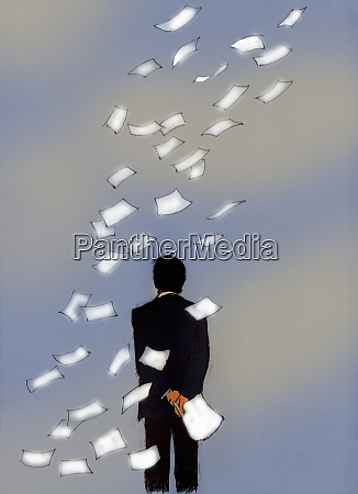 businessman watching papers blowing away