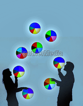 businessman and businesswoman juggling pie charts