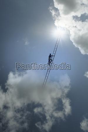 man climbing ladder between clouds in