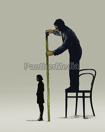 businessman measuring height of woman with