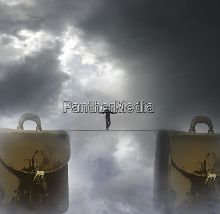 man walking tightrope between two briefcases
