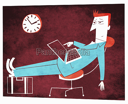 tired businessman with feet up using