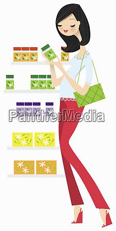woman reading label on herbal medicine