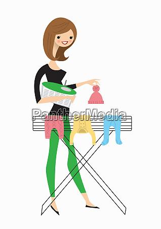 mujer colgando ropa de bebe en