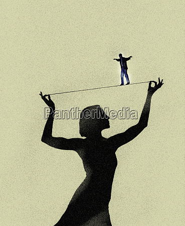 man walking tightrope supported by woman