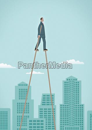 businessman on stilts walking above city