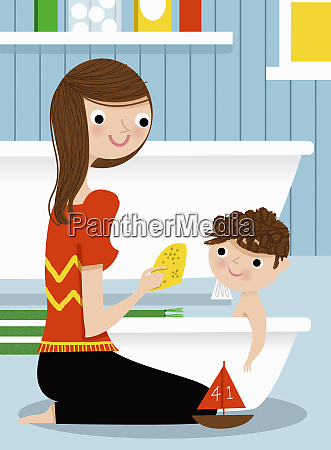 mother bathing son in baby bathtub