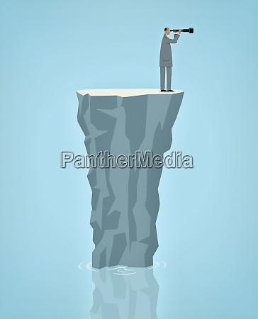 businessman stranded alone on rock in