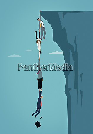 business people dangling over edge of