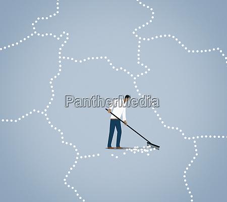 man raking up line of dots