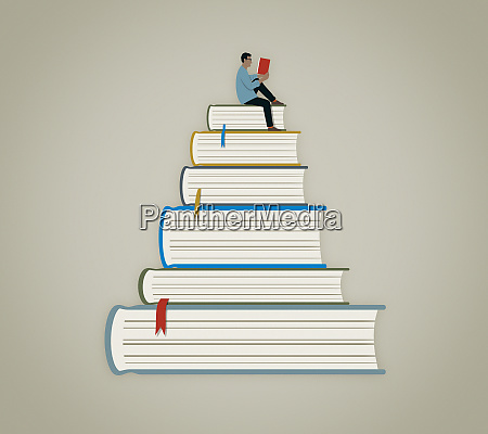 man sitting reading on top of