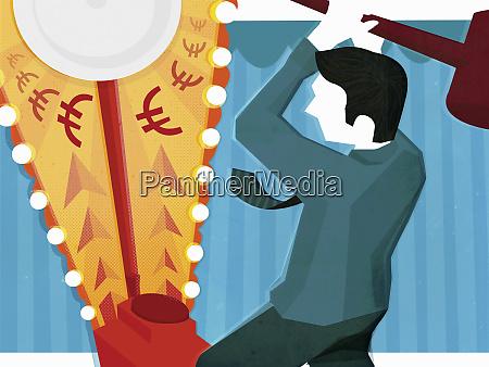 businessman swinging hammer at fairground strength