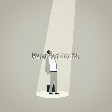 businessman looking up standing in spotlight