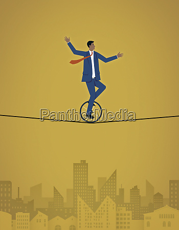 businessman riding unicycle across tightrope
