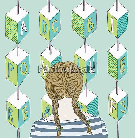 girl looking at alphabet blocks