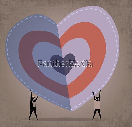 two women folding a large heart