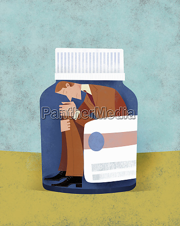 unhappy man trapped inside of pill